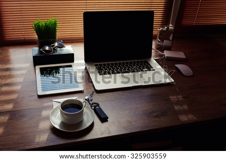 Mock up of office or home desktop with accessories and work tools, laptop computer and digital tablet with copy space screen, plant pot, cup of coffee, empty touch pad, modern hipster workspace table - stock photo