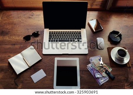 Mock up of rich successful business person with luxury accessories and work tools, cup of american coffee, sunglasses, open notepad, money, envelope, digital tablet and laptop computer with copy space