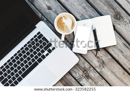Mock up of workspace on wooden desk with open laptop and white smartphone with blank screen, coffee cup and notebook