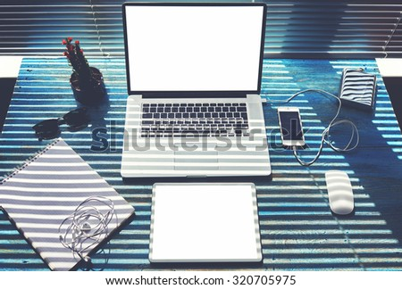 Mock up office or home desktop with accessories and work tools,blank screen laptop computer and digital tablet,mouse,sunglasses,phone charging,empty touch pad and headphones,modern freelance workspace - stock photo