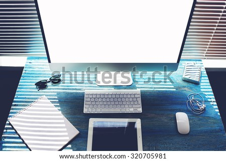 Mock up office or home desktop with accessories and work tools,blank screen laptop computer and digital tablet,mouse,sunglasses,phone charging,empty touch pad and headphones,modern freelance workspace