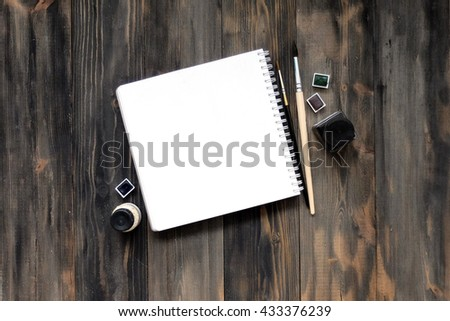 Mock up, photo paper on the table, art tools, white sheet, a wooden table. Background light wood