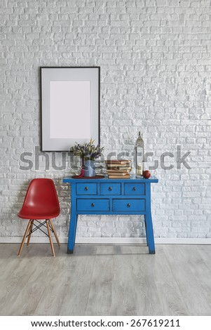 Mock up poster on table in room, old books - stock photo