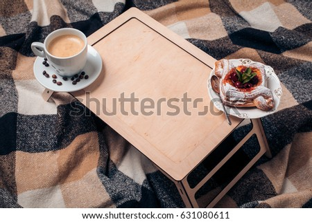 mockup of wooden table with coffee and pastry; top view of morning breakfast with bakery;