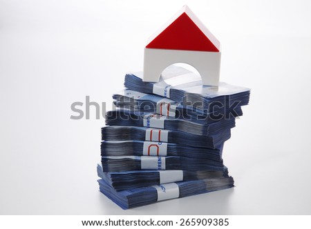 modal house on top of money stacked high - stock photo