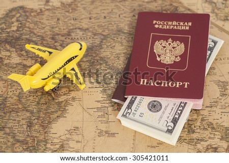 Model aircraft with Russian International passports and dollars on the world map background - stock photo