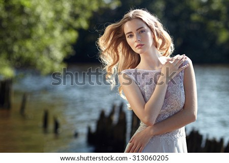 Model bride on the beach in the sunshine. Beauty, hair, style. - stock photo