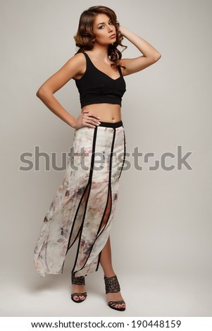 Model brunette with long curly hair. Studio photo