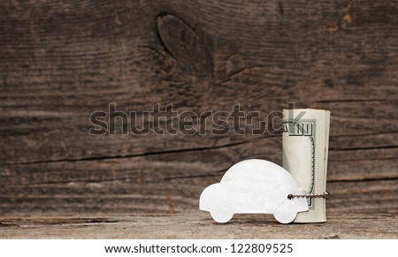 model car with silver chain over a lot of dollar bills on old wood background. space for your text - stock photo