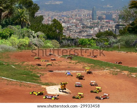model cars racing around a dirt track with a view of palm trees and the agbar tower of barcelona in spain