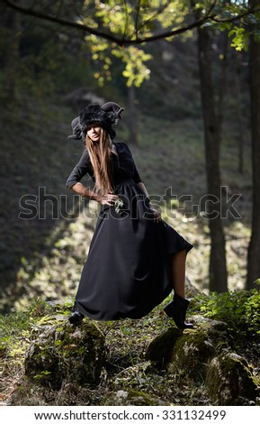 Model girl in a black dress and black hat walking in a mystical forest. Mystery, beauty, style, halloween.