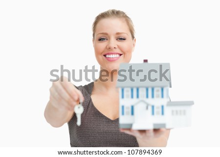 Model house and a key holding by a woman against white background - stock photo