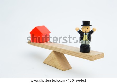 Model house and businessman balancing on a seesaw. Concept selling a house for the money - stock photo