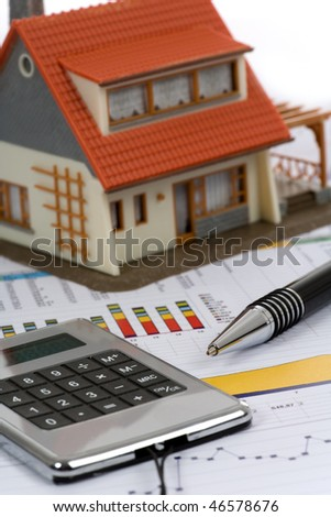Model house and calculator on construction plan - stock photo