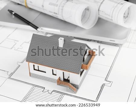 Model House and laptop on blueprint - stock photo