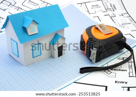 Model house and   tape measure on construction plan. House under construction concept. - stock photo