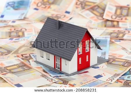 Model house on euro banknotes   - stock photo