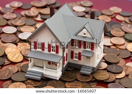 Model house on pile of coins â?? mortgage costs