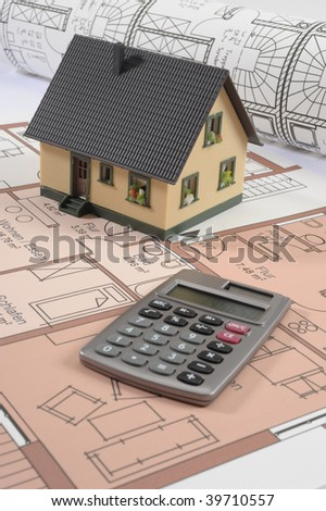 model house with pocket calculator on an house construction plan