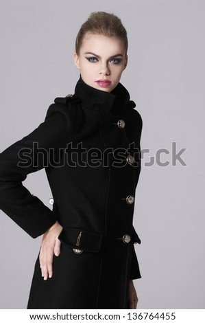 model in a black coat posing on gray background d - stock photo