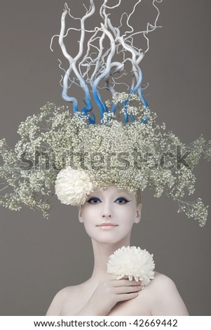 Model in an image of the winter, created by means of a make-up, Body- Art and floristics art on a white background - stock photo