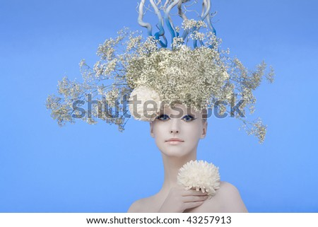 Model in an image of the winter, created by means of a make-up, Body-Art and floristics art on blue background. - stock photo