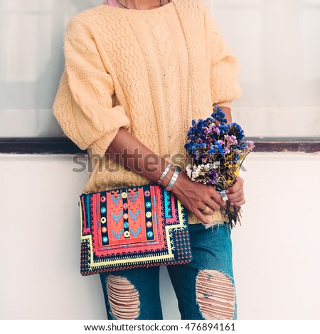 Model in autumn look. Knitted sweater.  Jeans.  Bright Accessories. Clutch. City Style.