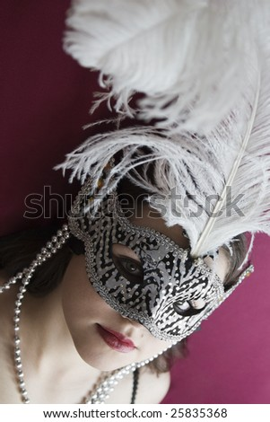Model in carnival mask looking at the camera. - stock photo
