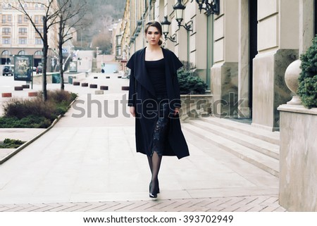 Model in nice clothes posing on the city street. Street fashion concept - portrait of a pretty girl with red lips wearing black cardigan, leather bag. Fashion blogger, toned style instagram filters