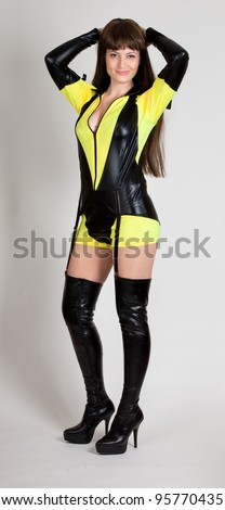 Model in sexy yellow and black outfit with thigh high boots and garter - stock photo