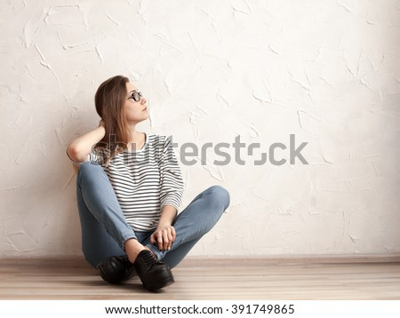 Model in striped shirt and jeans sitting on the floor