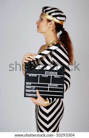 Model in stripy black-and-white dress and cap stands sideways, holds cinematographic plank - stock photo
