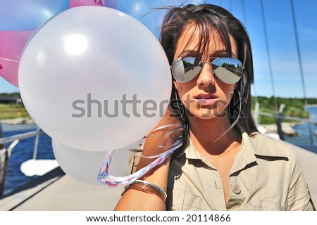 Model in sunglasses hold balloons outdoors.