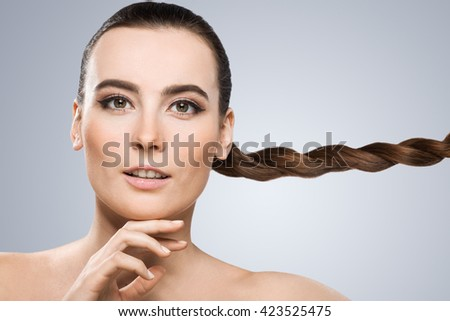 Model looking at camera and touching her chin. Nice make-up, looking lively with light smile. Pigtail aside. Beauty portrait, head and shoulders, closeup. Indoor, studio - stock photo