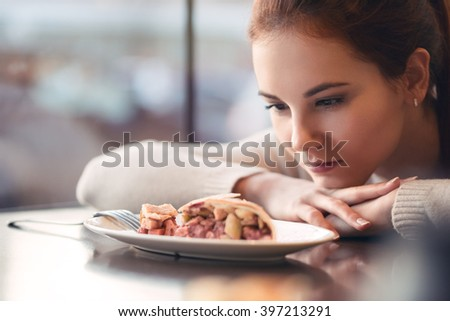 Model looks at a dessert in a cozy cafe