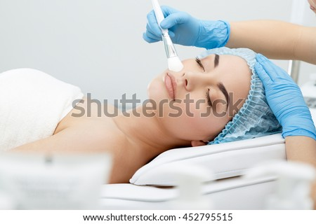 Model lying on couch with closed eyes. Hand in blue glove touching patient's face with brush. Cosmetological clinic. Healthcare, clinic, cosmetology