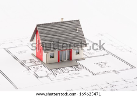 Model of a family house on a blueprint - stock photo