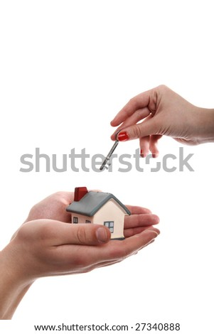 Model of a house in hands and a key in another - stock photo