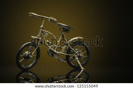 Model of bronze vintage bike on a sepia/brown background - stock photo