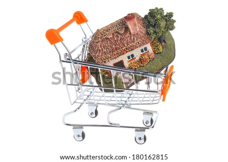 Model of house in the shopping cart isolated on white background - stock photo
