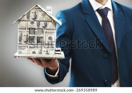 Model of house made of money in male hands on gray background - stock photo
