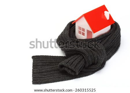 Model of house wrapped in dark scarf over white