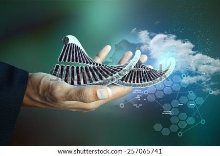 model of twisted chrome DNA chain and hand - stock photo
