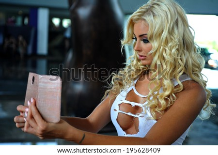 Model poses for her own phone snapshot wearing white ripped t-shirt tank - stock photo