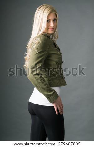 Model poses wearing leggings and jacket - stock photo