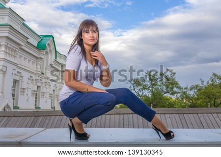 Model posing in front of tall historical building in old Russian style, full body sitting shot - stock photo