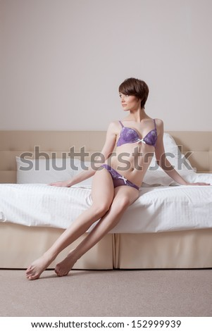 Model posing in purple lingerie, sitting on bed - stock photo