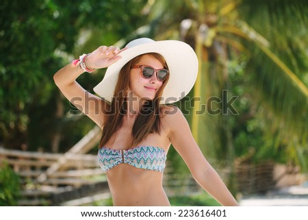 Model posing on a background of palm trees - stock photo