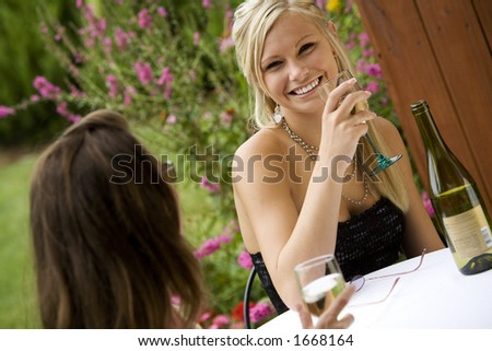 Model Release 351  Young women relaxing with a glass of wine in an outdoor cafe - stock photo