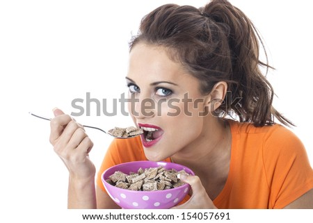 Model Released. Attractive Young Woman Eating Breakfast Cereal